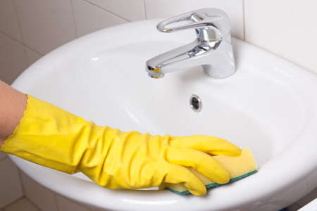 Hand in yellow glove with sponge cleaning white sink photo