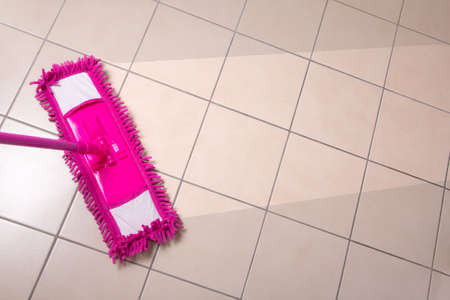 cleaning the tiled floor with pink mop photo