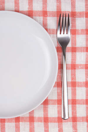 plate and fork over checkered tablecloth background photo