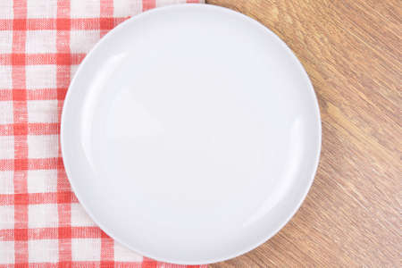 white empty plate on the wooden table with checkered tablecloth photo