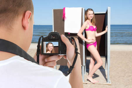slim beautiful woman in changing cabin and photographer on the beach photo