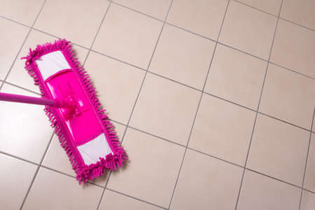 bright housekeeping: cleaning the tiled floor with pink mop Stock Photo