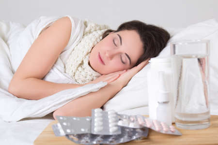 sick woman sleeping in bed and pills on the bedside table photo