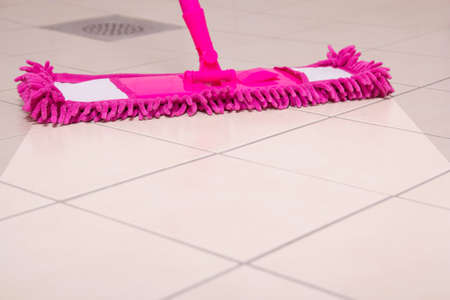 tiled floor: cleaning the tiled floor with pink mop Stock Photo