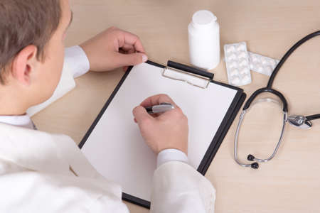 young male doctor prescribing treatment in modern office photo