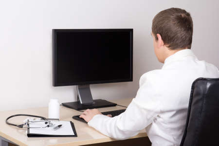 young male doctor working with computer in modern office photo