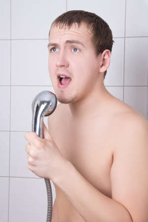 young attractive and funny man sinfing in the shower