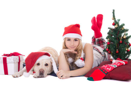 attractive teenage girl in pajamas lying with dog in santa hat isolated on white background photo