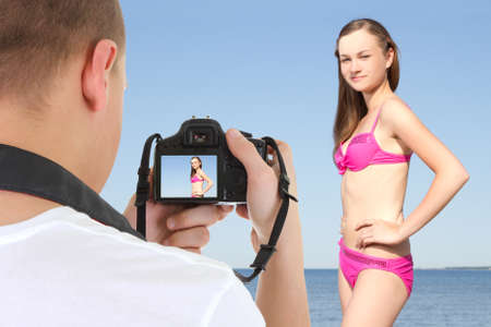 photographer with dslr camera taking picture of young beautiful woman on the beach photo