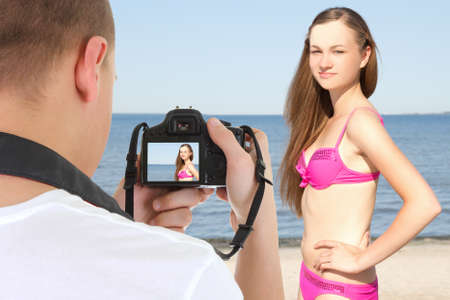 photographer with camera taking picture of young beautiful woman on the beach photo
