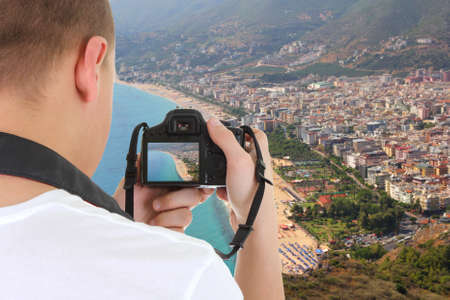 camera in male hands taking picture of beautiful landscape in Alanya, Turkey photo
