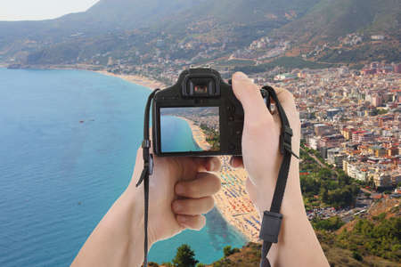 camera in male hands taking picture of beautiful landscape in Turkey photo