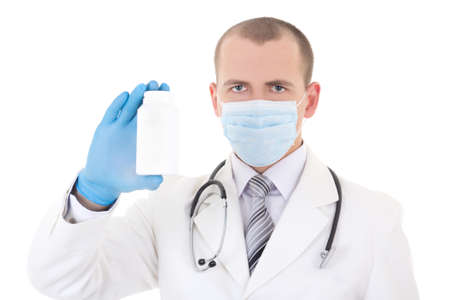 young doctor in mask holding bottle of pills isolated on white background photo