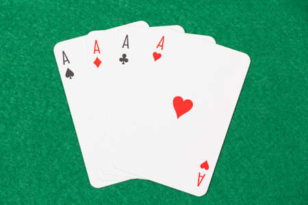 playing cards - four aces on green table Stock Photo