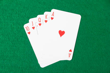 Poker cards with royal flush combination on green table photo
