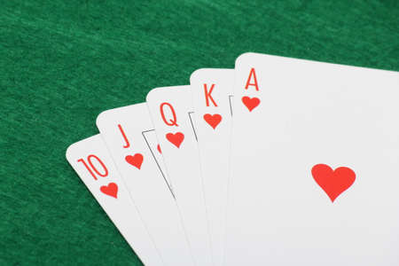 Poker cards with royal flush combination on green casino table photo