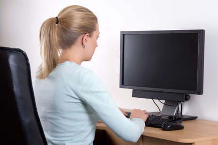 desktops: back view of young woman with personal computer in office