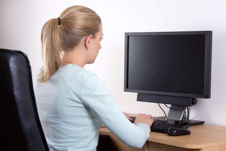 looking at view: vista posteriore di giovane donna con il personal computer in ufficio