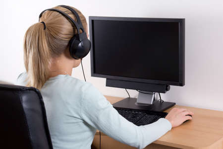 person on computer: back view of young blondie woman using a computer and listening music in headphones Stock Photo