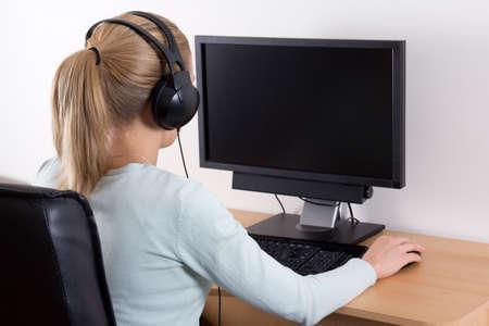 trabajando en computadora: Vista posterior de la joven mujer rubia utilizando un ordenador y escuchar m�sica en los auriculares Foto de archivo
