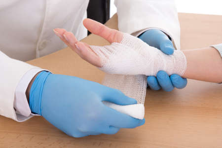 wound care: close up of male doctor bandaging female hand