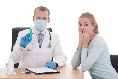 young doctor in mask with syringe and terrified female patient isolated on white background photo