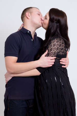 young beautiful pregnant woman and her husband kissing over grey background photo