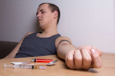 stoned: heroin, syringe, spoon, lighter on the table and stoned male addict sitting in room