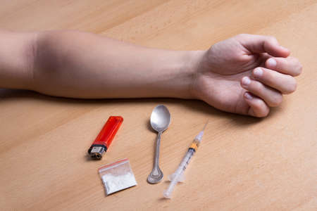 relapse: close up of addicts hand on the table with drugs, syringe, spoon and lighter