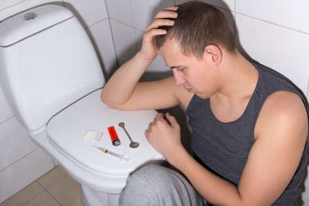 young stoned man with heroin addiction in bathroom photo