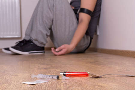 relapse: syringe with drugs and stoned addict sitting on the floor