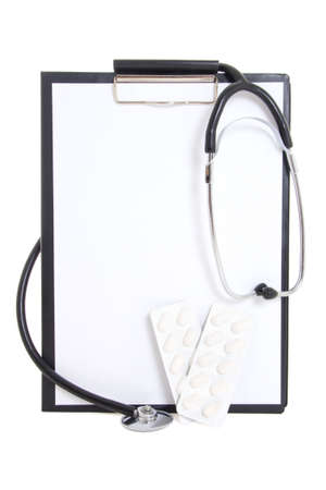plastic clipboard with blank paper sheet, tablets and stethoscope isolated on white  photo