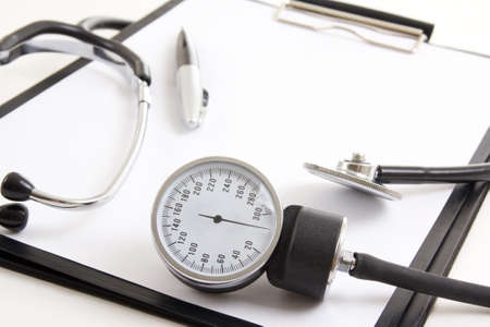 close up of clipboard with blank paper sheet, stethoscope and sphygmomanometer isolated on white  photo