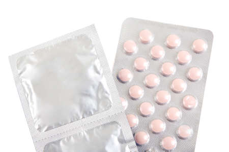 birth control pills and condoms over white  Stock Photo