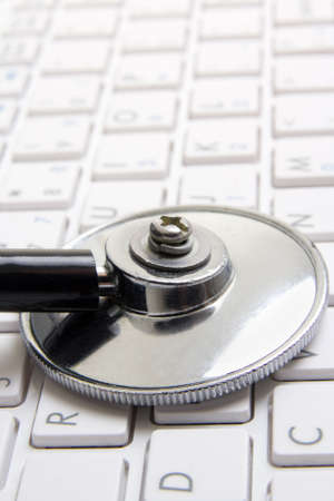 close up of stethoscope on white notebook keyboard photo