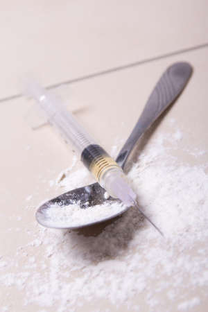 morphine: close up of syringe with drug substance, heroin powder and spoon on the floor