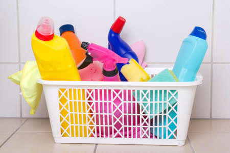 cleaning supplies in plastic box on tiled floor in bathroom photo