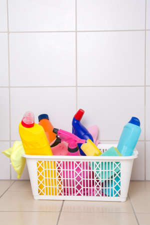 cleaning supplies in plastic basket on tiled floor in bathroom photo