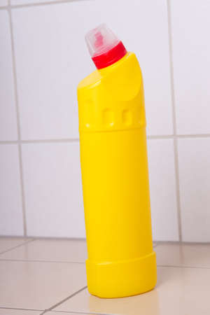 yellow plastic bottle of cleaning product on tiled floor in bathroom photo