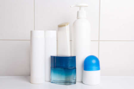 set of cosmetic bottles over white tiled wall in bathroom photo