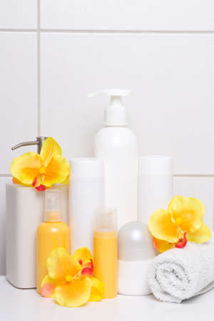 set of cosmetic bottles with orange flowers over white tiled wall in bathroom photo