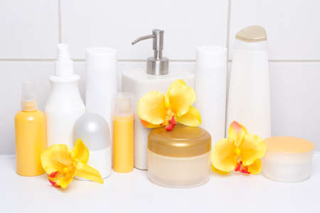 set of white cosmetic bottles and hygiene supplies with orange orchids over tiled wall in bathroom photo