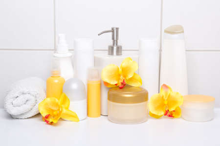 collection of white cosmetic bottles with orchids over tiled wall in bathroom photo