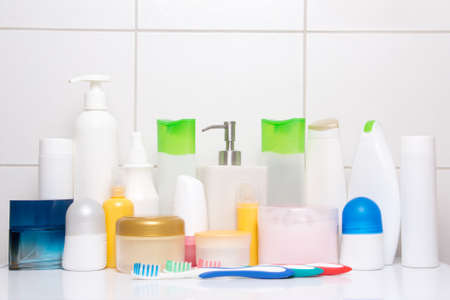 set of colorful cosmetic bottles over white tiled wall in bathroom photo