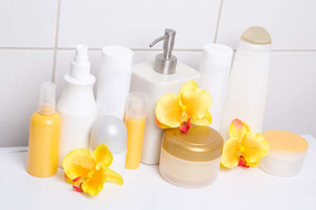 collection of white cosmetic bottles and hygiene supplies with orange orchids over tiled wall in bathroom photo