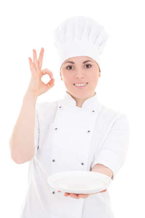 portrait of young baker woman in uniform with empty plate showing ok sign  isolated on white background photo