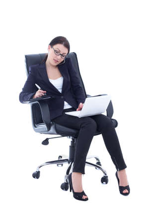 young business woman sitting on chair, working with laptop and talking on the phone isolated on white background photo