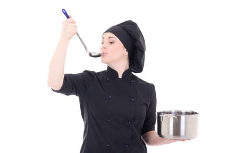 portrait of young cook woman in black uniform holding pan and tasting food isolated on white background photo