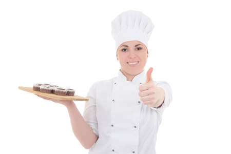 young attractive cook woman in uniform with chocolate muffins thumbs up isolated on white background photo