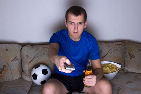 football supporter in uniform sitting on the sofa and changing channels with remote control photo